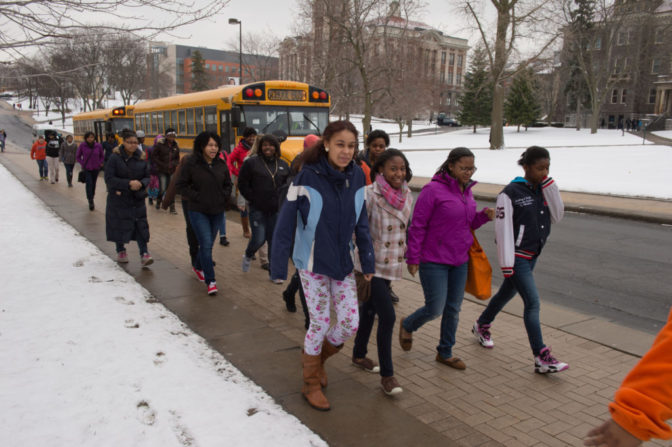 Cultural Excursions: Girls walk down the sidewalk away from a yellow school bus