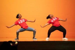 Two women on stage in red shirts with the Delta Sigma Theta logo in white, leaning to the left as they do a step performance in front of a yellow backdrop