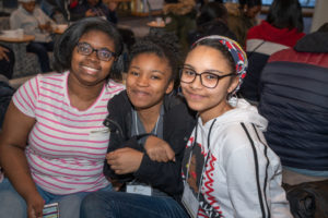 Three girls sit together smiling at the camera